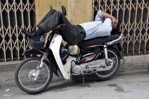Bild: Motorradfahrer auf Moped schlafend in Hanoi