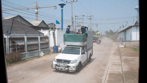 Maeklong Railway parallel zur Straße in Dörfern