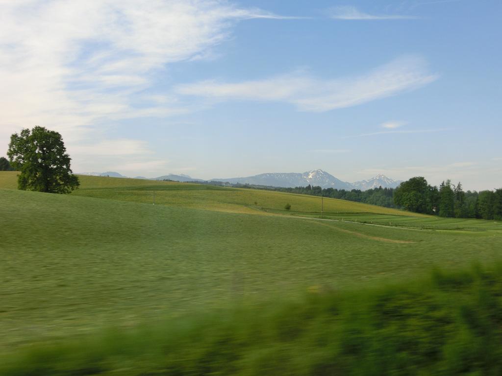 Bild: Schnappschuss aus dem Zug auf Wiesen und Berge in Oberbayern