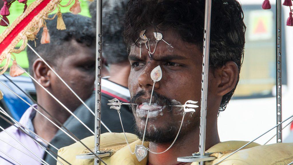 Junger Mann mit durchstochener Zunge und Wangen bei Thaipusam in Singapur (Little India)