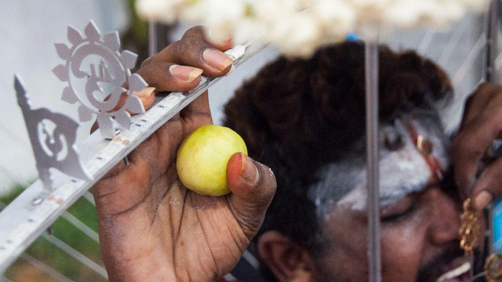 Durchstoßen der Zunge mit einem Metallstab als Vorbereitung für Thaipusam in Singapur
